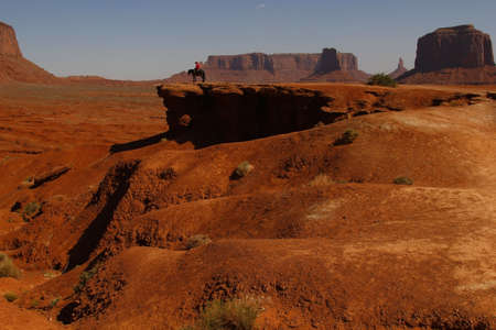 Cowboy on his horse against the fantastic shapes of the vast sandstone buttes of Monument Valley, part of the Colorado Plateau in the Navajo Nation Reservation, Utah, USA