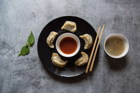 Popular snacks of south east Asia momos on a black plate along with condiments.