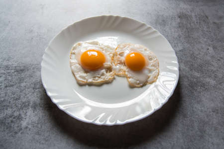 Egg poach sunny side up a healthy food ingredient on a plate. Close up, selective focus. Banque d'images