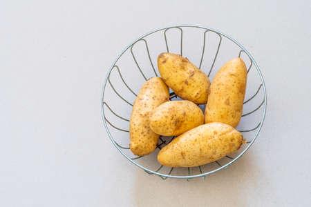 Uncooked Irish Potatoes in a round metal basket
