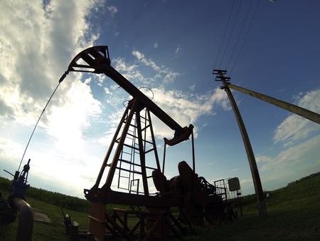 brink: Pump jack starting the lifting stroke to brink crude oil up out of a producing oil well Stock Photo