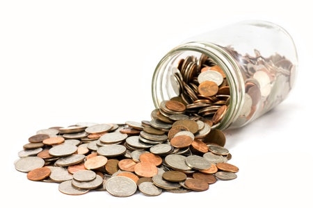 money jar: A spilled jar of US coins on a white background. Stock Photo
