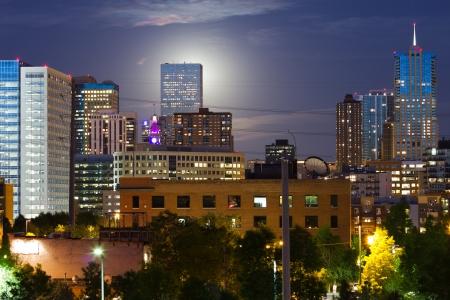 An eerie glowing moon rises behind a tall skyscraper in the Denver Colorado skyline. Archivio Fotografico