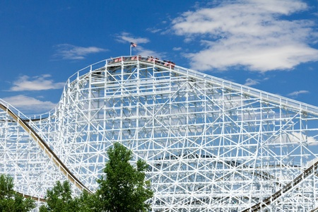 A wooden roller coaster reaches the top of a big hill while an American flag waves above it. photo