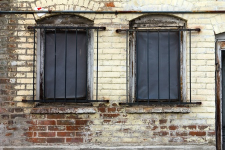 Dirty old window with bars on a grungy brick building. photo