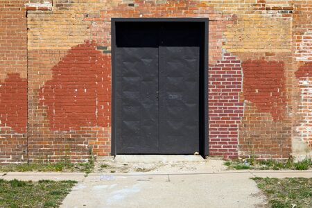 abandoned warehouse: Big metal door in an old brick warehouse with city sidewalk in front
