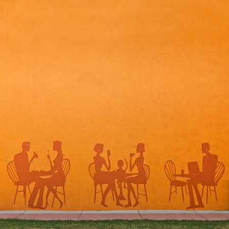 Silhouettes of people eating in a restaurant on an orange wall with a city sidewalk in front