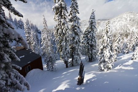 Mountain cabin burried in a mountain of snow after a winter blizzard near Lake Tahoe California Nevada photo