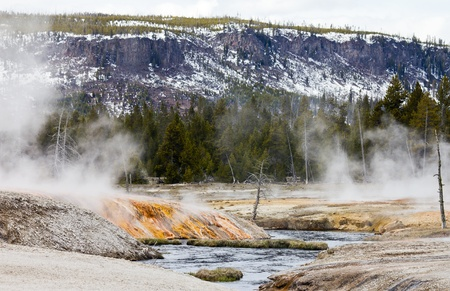 A series of active geothermal geysers drain into the Firehole River in Yellowstone National Park, Wyoming USA photo