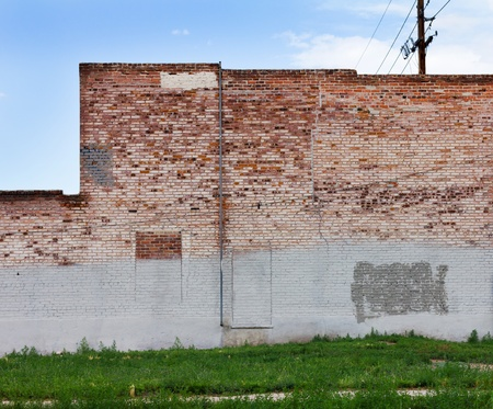 A grungy red brick wall of an old abandoned warehouse in downtown Denver Colorado  Stock Photo