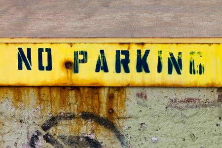 no parking: No Parking sign painted on a grungy old wall on an abandoned urban building