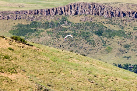 A paraglider soars daringly above Golden Colorado