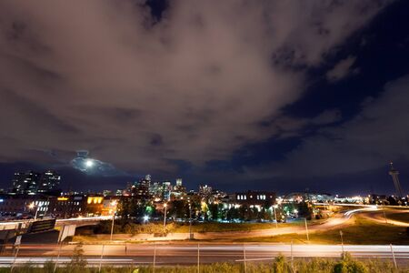 mile high city: Denver skyline with the full moon rising at night