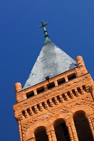 Cross on a church steeple isolated against a blue sky background photo