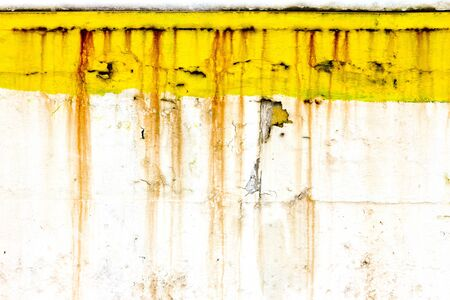 dripping paint: Grungy old wall with peeling yellow paint and dripping rusty lines creates unique background texture. Stock Photo