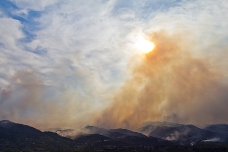 wildfire: Smoke clouds rise from a burning wildfire in the Colorado mountains Stock Photo