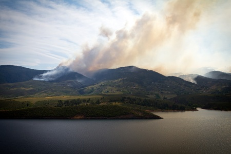 Wildfire smoke rises on burning mountains in Colorado