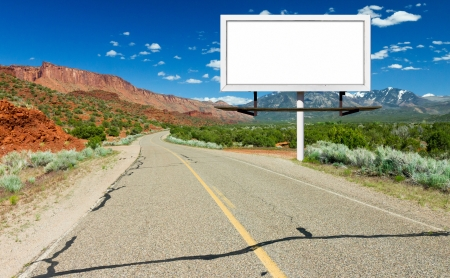 Blank billboard sign by empty highway through desert landscape photo