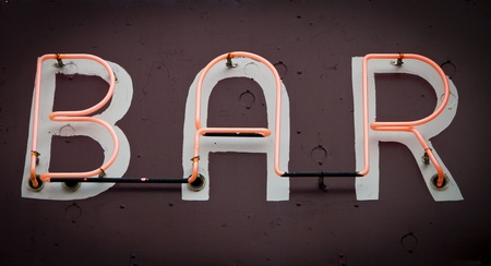 Bar Sign with glowing neon fluorescent letters on old grungy background texture Stock Photo