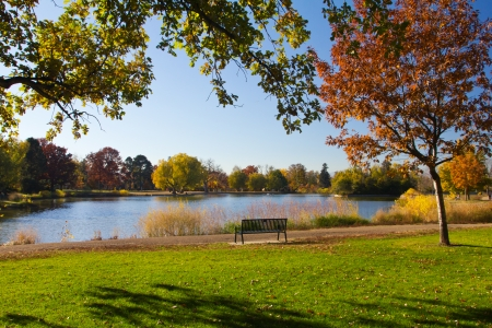 denver colorado: Empty park bench by scenic lake in the fall