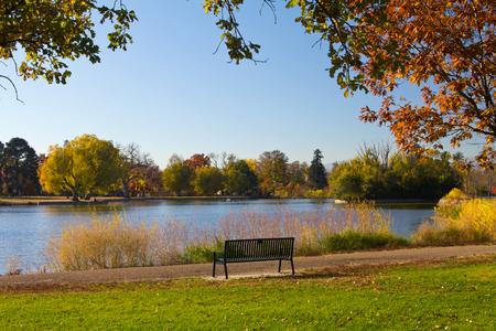 denver: Empty bench by lake and Fall trees - Washington Park - Denver, Colorado Stock Photo