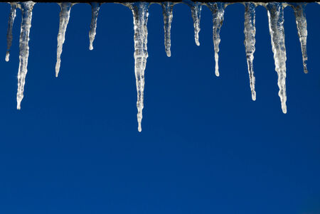 Frozen icicles hanging from a roof isolated against a blue sky backgroud photo