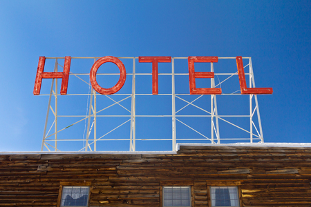 old sign: Vintage hotel sign above an old wooden cabin in the Colorado Rocky Mountains Stock Photo