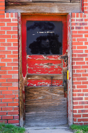 tenement: Old red door entrance to abandoned building