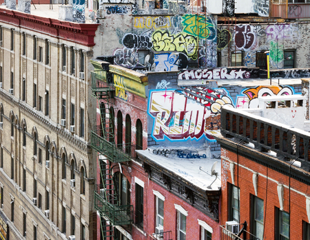window graffiti: New York City block of apartment buildings with graffiti covered roof tops