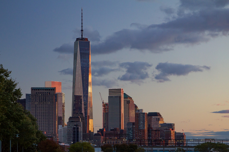 trade off: Sunset light relfects off the the World Trade Center tower in lower Manhattan, New York City Stock Photo