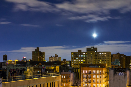 queens: New York City rooftop skyline view at night with moon rising above