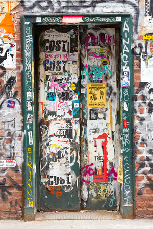 vandalize: NEW YORK CITY – CIRCA 2015: Graffiti paint and stickers cover a hidden doorway in empty old building in the Soho area of Manhattan in New York City. This neighborhood is home to many artists lofts and art galleries.