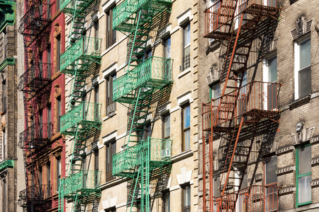 brick building: New York City Block of Colorful Apartment Buildings with Fire Escapes in Manhattan