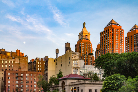 sunset city: Moon rising in the sky above Union Square Park at sunset in Manhattan, New York City