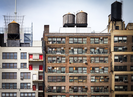 roof windows: Old vintage apartment buildings with wall of windows and water towers on the roof tops in downtown New York City