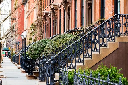 Reihe der alten Brownstonegebäude entlang einem leeren Bürgersteigblock in der Greenwich Village-Nachbarschaft von Manhattan, New York City NYC