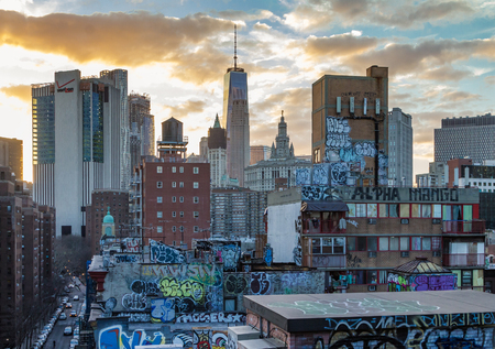 NEW YORK CITY - FEBRUARY 24: The sun sets behind the Skyscrapers of the Manhattan skyline and the graffiti covered rooftops of Chinatown in New York City on February 24th, 2017. Editorial