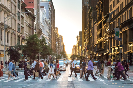 NEW YORK CITY - CIRCA 2017: Busy crowds of people cross the intersection of 5th Avenue and 23rd Street in Manhattan, New York City with the colorful setting sun in the background on June 3rd, 2017. Sajtókép