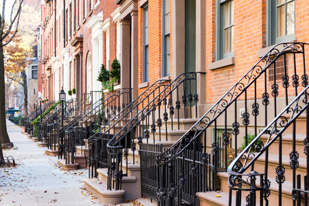 Row of old historic brownstone buildings along an empty sidewalk block in the Greenwich Village neighborhood of Manhattan, New York City NYC