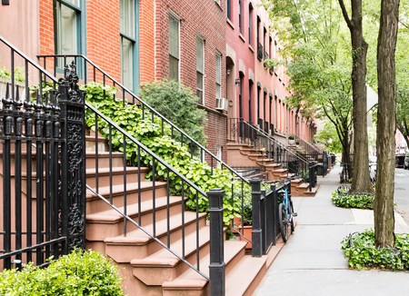 Scenic tree lined street of historic brownstone buildings in the West Village neighborhood of Manhattan in New York City, NYC USA Stock Photo