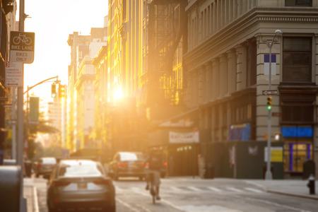 配達人ダウンタウンの建物の窓に反射した太陽の光でニューヨーク市の通りを自転車に乗る