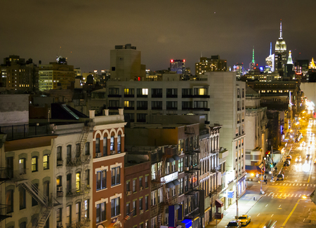 Overhead view of Bowery Street through the Chinatown neighborhood of New York City with the Midtown Manhattan Skyscrapers in the distant skyline at night