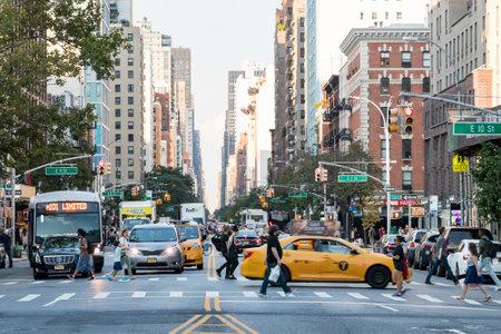 NEW YORK CITY - CIRCA 2017: Drukke mensen lopen over een kruispunt tijdens het spitsuur op 3rd Avenue voor de auto's gestopt bij een verkeerslicht in Manhattan, New York City in 2017.