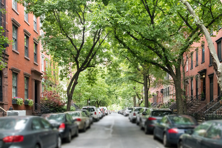 Tree lined street of historic brownstone buildings in a Greenwich Village neighborhood in Manhattan New York City NYC 写真素材