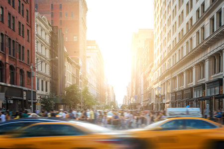 Fast paced motion in New York City as yellow taxi cabs speed down 5th Avenue with crowds of busy people walking across the intersection at 23rd Street in Manhattan with sunset light in the background Stockfoto