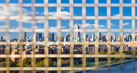 New York City skyline seen through the bars of a fence on the Williamsburg Bridge between Brooklyn and Manhattan