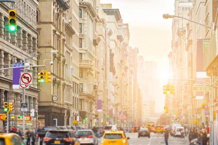 Sunlight shines on Broadway in New York City with people and cars lining the street through Midtown Manhattan