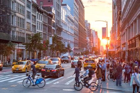 NEW YORK CITY - 7 GIUGNO 2018: L'intersezione tra 23rd Street e Broadway è piena di persone e automobili mentre i tramonti sullo sfondo dell'orizzonte di Manhattan.