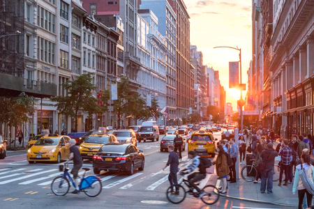 NEW YORK CITY - JUNE 7, 2018: The intersection of 23rd Street and Broadway is busy with people and cars while the sunsets in the background horizon of the Manhattan skyline.