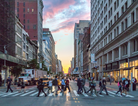 Crowds of people crossing an intersection in Manhattan, New York City with the colorful light of sunset in the background 報道画像